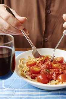 Man eating spaghetti with tomato sauce, close-up - HAWF000845