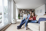 Relaxed couple at home on couch looking out of window - RBF003529