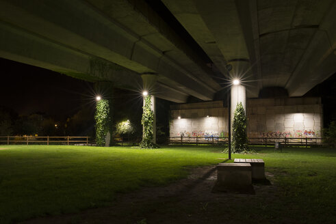 Spain, Naron, park under highway bridge lighted by street lamps at night - RAEF000371