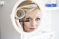 Mirror image of blond woman with curler applying mascara - CHPF000161