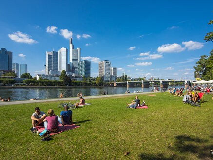 Germany, Hesse, Frankfurt, People at River Main with skyline in background - AM004148