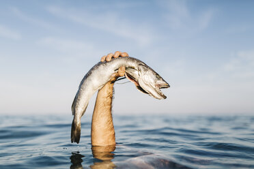Man's hand holding caught fish out of the water - JRFF000019