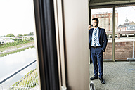 Young businessman with cell phone looking out of window - UUF005408