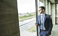 Young businessman with cell phone looking out of window - UUF005411