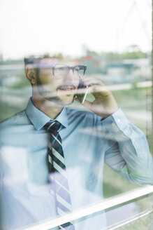 Young businessman on cell phone behind windowpane - UUF005449
