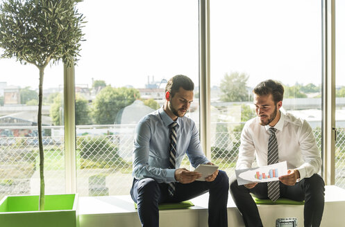 Two young businessmen looking at document and digital tablet - UUF005485