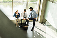 Three young business people discussing document - UUF005494