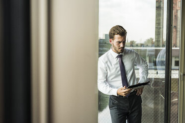 Young businessman looking at digital tablet - UUF005522