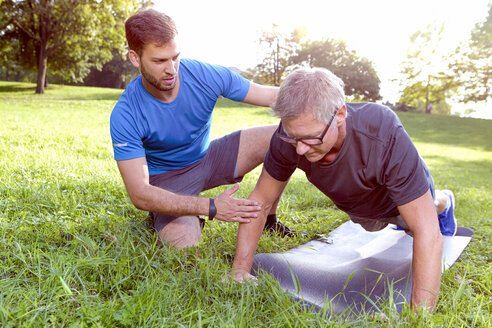 Man doing pushups on a meadow while his personal trainer watching him - SEGF000410