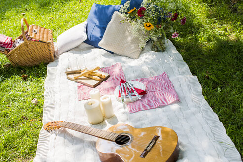 Picnic blanket with guitar, candles and cushions on a meadow - KSWF001561