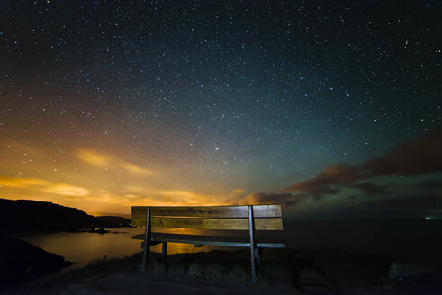 Spain, Ortigueira, Loiba, bench under starry sky with blue ray - RAEF000386