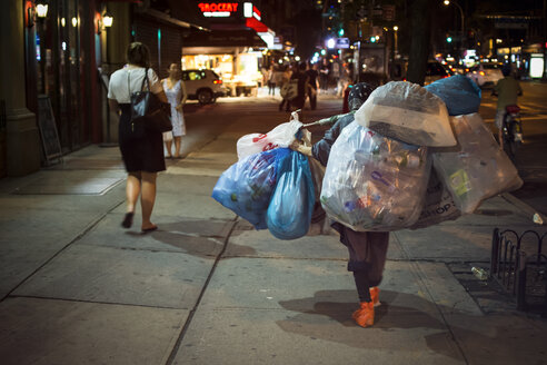 USA, New York City, Homeless woman carrying plastic bags - ON000870