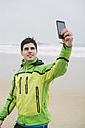 Spain, Valdovino, young jogger taking a selfie with smartphone on the beach at rainy day - RAEF000388