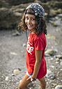 Spain, Gijon, portrait of smiling little girl on rocky beach - MGOF000560