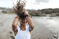 Spain, Gijon, little girl on the beach holding her blowing hair - MGOF000539