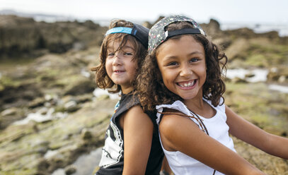Spain, Gijon, portrait of smiling little girl and her friend sitting back to back at rocky coast - MGOF000545