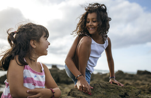 Spain, Gijon, portrait of two smiling little girls playing at rocky coast - MGOF000549