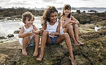 Spain, Gijon, group picture of three little girls sitting at rocky coast - MGOF000561