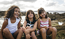 Spain, Gijon, group picture of three little children sitting at rocky coast - MGOF000552