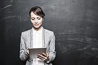 Portrait of a dark haired businesswoman using digital tablet - FMKYF000612