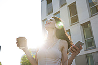 Woman listening to music from smart phone holding coffee cup - FMKYF000621