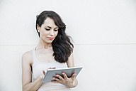 Young woman using digital tablet leaning on wall - FMKYF000623