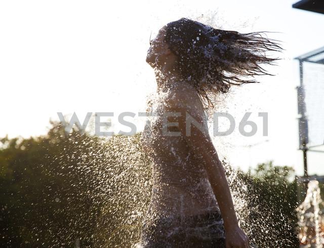 Woman running through fountain splashing water drops - FMKYF000624