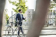 Young businessman pushing bicycle, holding smart phone - UUF005562