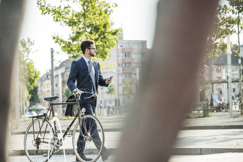 Young businessman pushing bicycle, holding smart phone - UUF005562