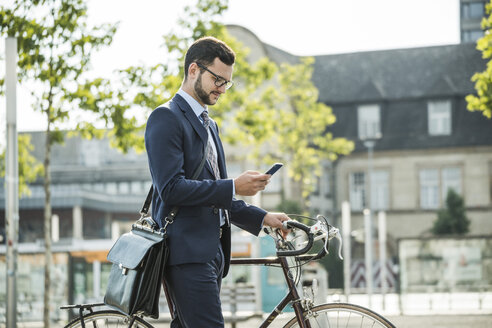 Young businessman pushing bicycle, holding smart phone - UUF005564