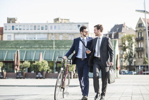 Two businessmen with bike and smart phone walking in the city - UUF005570