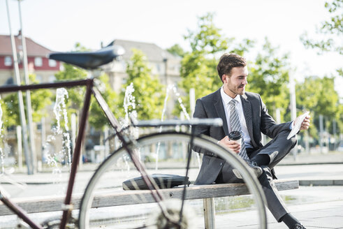 Young businessman sitting on bench using digital tablet - UUF005583