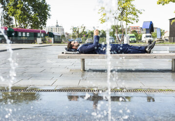 Young businessman lying on bench, working - UUF005587