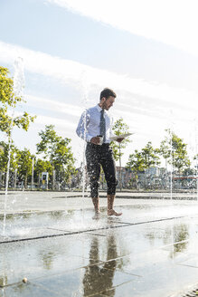 Young businessman standing in fountain, reading documents - UUF005593