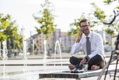 Young businessman sitting cross-legged on bench, using smartphone - UUF005595