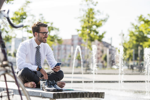 Young businessman sitting cross-legged on bench, using smartphone - UUF005596