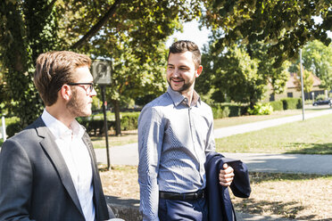 Two young businessmen walking together - UUF005601