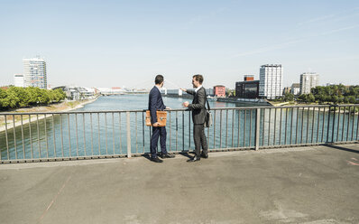 Young businessmen standing at railing looking at river - UUF005609