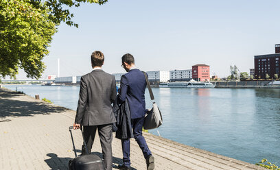 Two young businessmen on a business trip, walking by river - UUF005615
