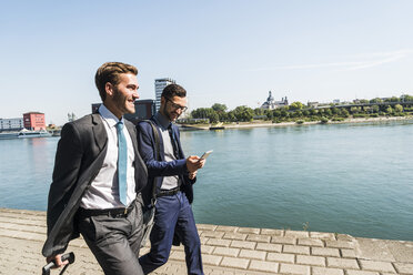Two young businessmen on a business trip, walking by river - UUF005617