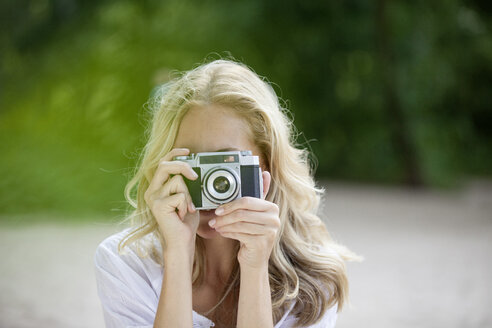 Blond woman taking a photo with an old camera - FMKF002065