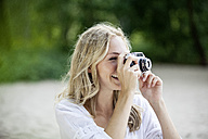 Smiling blond woman taking a photo with an old camera - FMKF002066