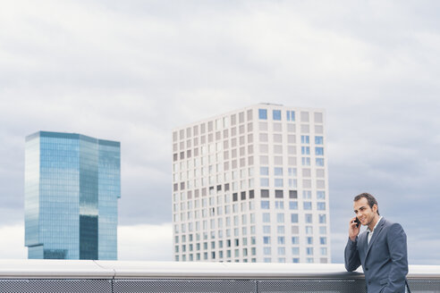 Businessman on urban balcony talking on cell phone - BZF000216