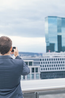 Young man with suit taking photos at business building - BZF000227