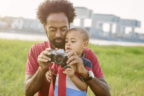 Germany, Cologne, father explaining camera to his son in a field - MADF000634