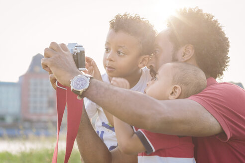 Father explaining camera to his sons outdoors - MADF000756