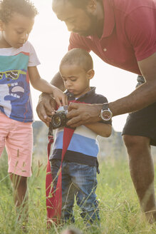 Father explaining camera to his sons in a field - MADF000637
