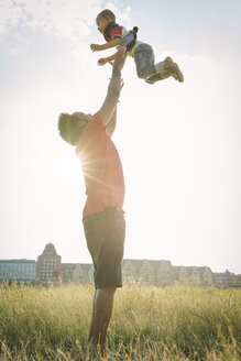 Germany, Cologne, father throwing up his son in a field - MADF000643
