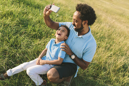Father and happy son in a field taking a selfie - MADF000653