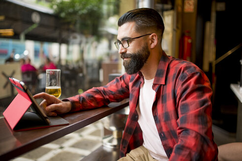 Adult bearded hipster style man touching tablet in bar and drinking alchohol near to window - JASF000015